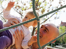 dad-helping-his-little-daughter-to-climb-ladder-smiling-father-playing-playground-44108805