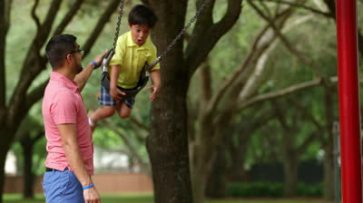 stock-footage-a-cute-little-hispanic-boy-laughs-happily-while-his-dad-pushes-him-on-a-playground-swing